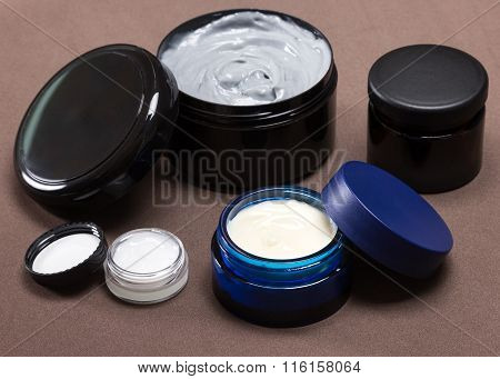 Several Jars Of Different Sizes Filled With Creams