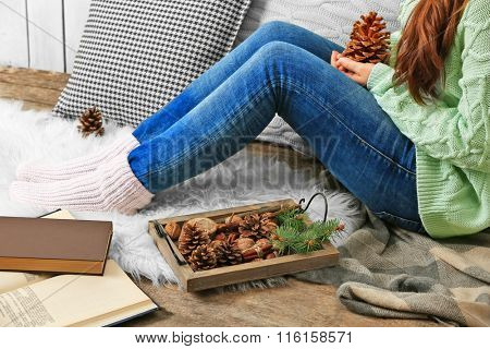 Woman holding pine cone, books and wooden basket with evergreen