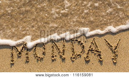 Inscription MONDAY on a gentle beach sand with the soft wave (days of the week series)