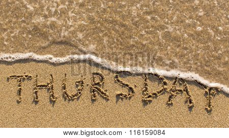 Inscription THURSDAY on a gentle beach sand with the soft wave (days of the week series)