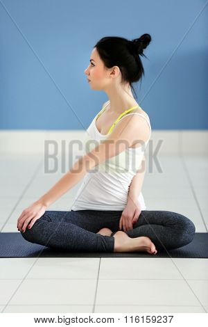 Health concept. Young attractive woman does yoga exercise in the room against blue wall