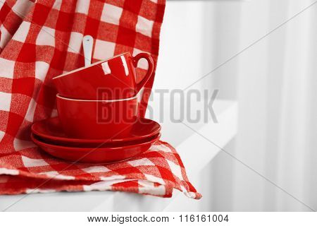 Red cups, saucers and napkin on a white background, close up
