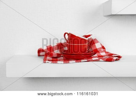 Red cups, saucers and napkin on a white background