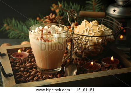 Cup of hot cacao with marshmallow and cookies on coffee beans