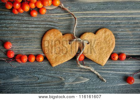 Heart shaped biscuits with ash berries and thread on wooden background, top view