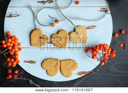 Heart shaped biscuits with ash berries on a round mat, top view