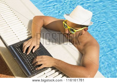 Man working on laptop at the swimming pool edge. Top down viewpoint
