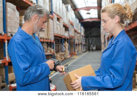 Man using wrist computer to scan and log parcel