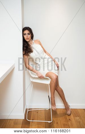 elegant young woman in white cocktail sit on chair , indoor shot