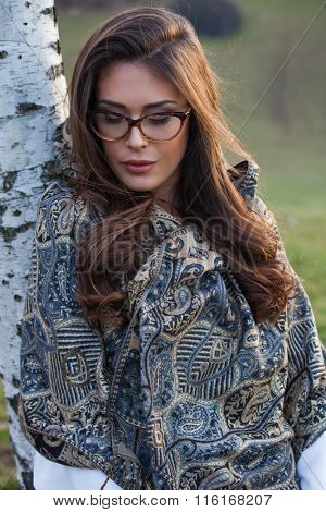 young woman with eyeglasses and cashmere scarf portrait, outdoor winter day