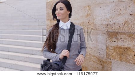 Grinning woman in sweater near wall looking over