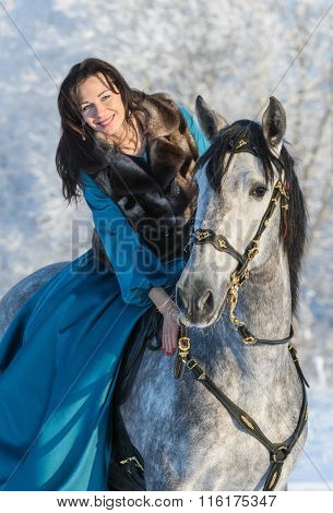 Woman in a blue dress riding on a grey Spanish horse
