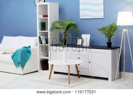 Room interior with commode, bookcase, table and sofa on blue wall background