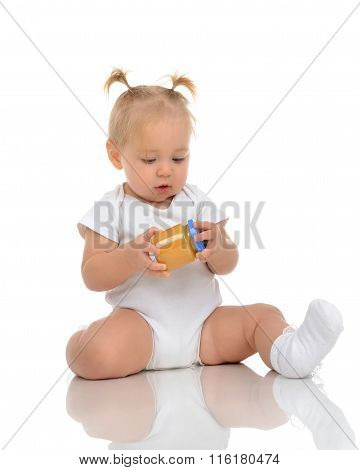 Infant Baby Girl Kid Sitting And Holdingin Hands Jar Of Child Mash Puree Food