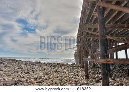 Large waves crashing under the pier.