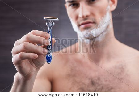 Attractive young man is presenting new shaver