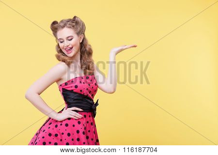 Beautiful pin-up girl is presenting something interesting