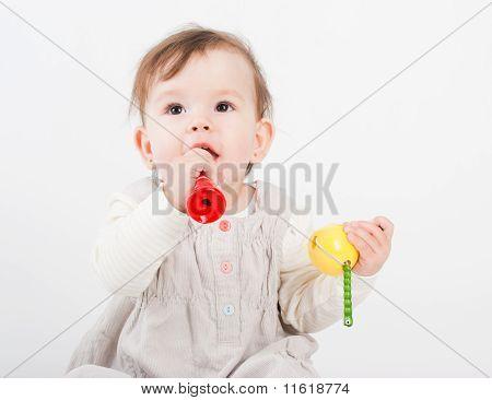 Das kleine Mädchen spielt mit Holzspielzeug weißen Hintergrund
