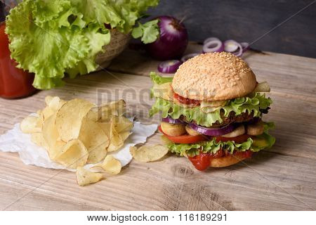 Juicy cheeseburger on wooden table with potato chips and ketchup.