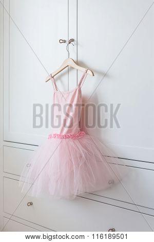 Girl's Dress Hanging On White Wooden Wardrobe