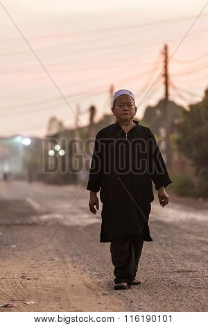 Man Dressed In Traditional Islamic Clothing Walks Down The Road At The Muslim District Of Siem Reap