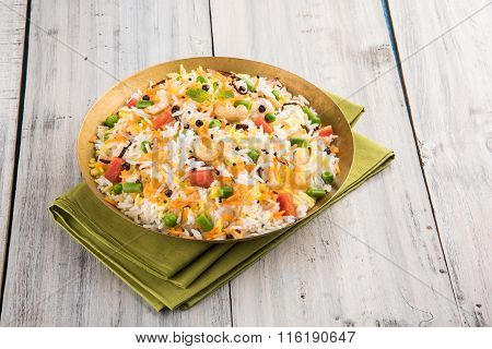 Veg biryani or veg pulav served in a round brass bowl over wooden background