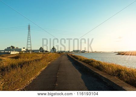 Road Along A River At Sunset Time.