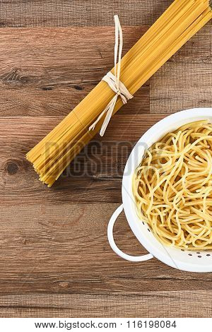Overhead view of cooked and dried spaghetti. The cooked pasta is in a colander and the raw is tied with raffia. Horizontal on a wood kitchen table.