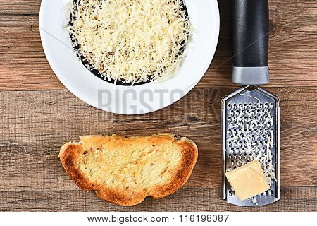 High angle view of a piece of garlic bread and a bowl of grated parmesan cheese with a grater and lump of cheese.