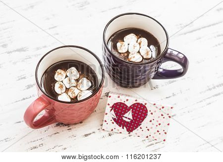 Two Cups Of Hot Chocolate With Marshmallows And  Valentine's Day Poscard On Bright Wooden Surface