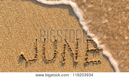 Inscription JUNE on a gentle beach sand with the soft wave (months of the year series)