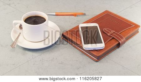 Brown Organizer, White Coffee Cup, Mobile Phone, Grey Background