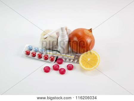 Thermometer, pills, onion, garlic, lemon