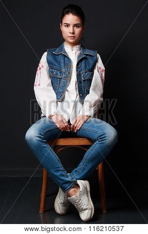 Impudent  Brunette Woman In Jeans Vest Sitting On The Chair
