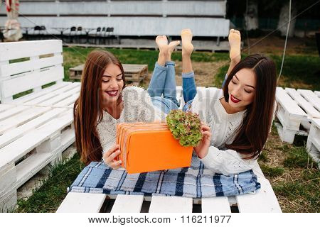 Girls lie on the bench and give each other gifts