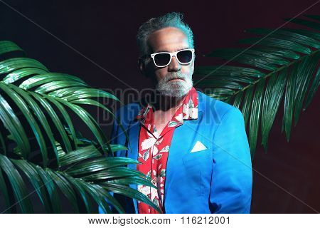 Stylish Senior Businessman Between Palm Leaves