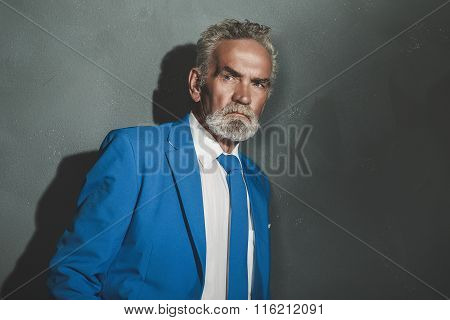 Serious Matured Businessman Leaning Against Wall
