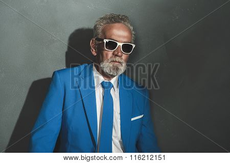 Senior Businessman With Shades Against Gray Wall