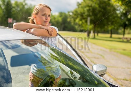 Young woman standing by her new car