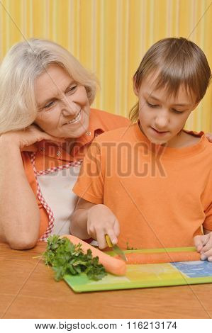 Elderly woman and a boy  in the kitchen