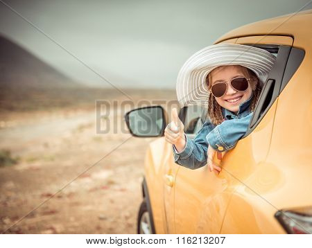 little girl traveling by car in the mountains
