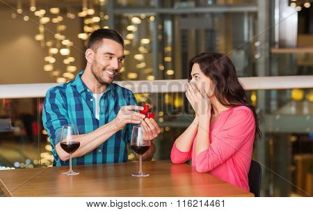 man giving engagement ring to woman at restaurant