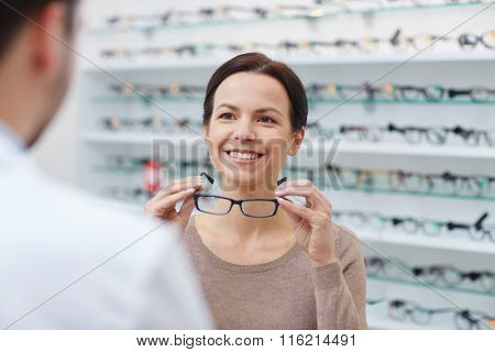 woman showing glasses to optician at optics store