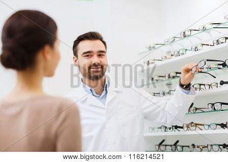 woman and optician showing glasses at optics store