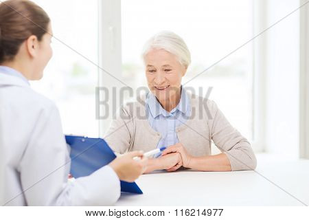 doctor with clipboard and senior woman at hospital