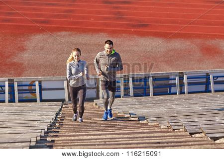 happy couple running upstairs on stadium