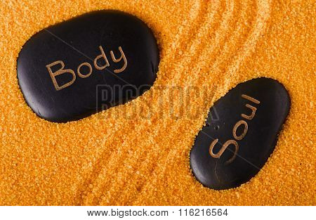 Couple Of Black Lava Stones In Yellow Sand
