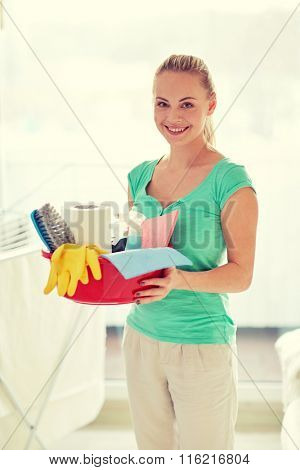 happy woman holding cleaning stuff at home