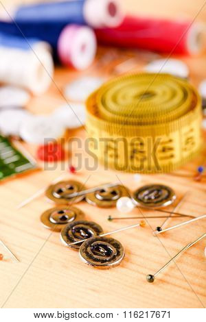 Several Metal Buttons In Front Of Other Sewing Accessories
