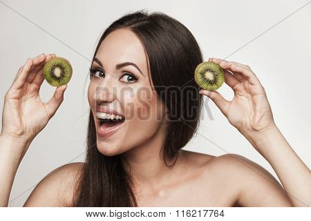 Funny Portrait Of Young Woman Holding Kiwifruit